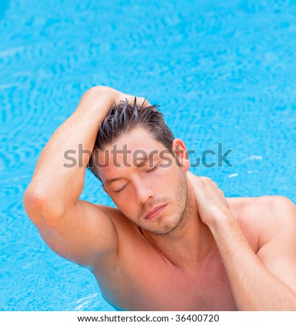 Cheerful good-looking wet hair man in the blue pool relaxing - stock photo