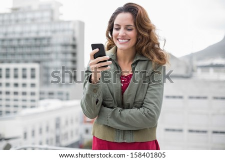 Cheerful gorgeous brunette in winter fashion holding smartphone on urban background - stock photo