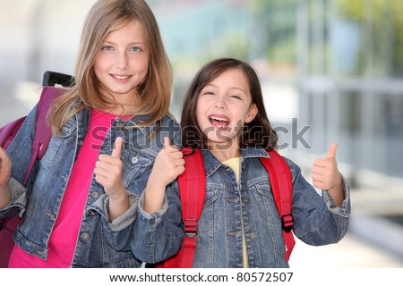 Cheerful grade-schoolers going back to school - stock photo