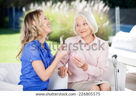 Cheerful granddaughter showing cards to grandmother while playing at nursing home porch - stock photo
