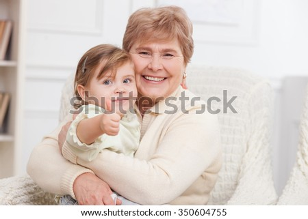 Cheerful grandmother is caring of her granddaughter. They are sitting on the sofa and embracing. The girl is giving thumb up. They are smiling - stock photo