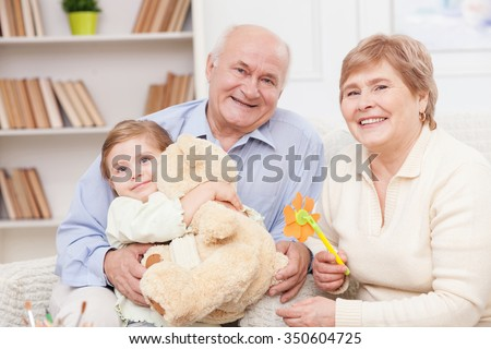 Cheerful grandparents are taking care of their granddaughter. The old man is sitting and holding the child. The girl is embracing teddy bear. They are smiling - stock photo