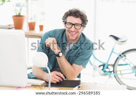 Cheerful graphic designer using a graphics tablet in a modern office - stock photo