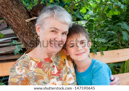 cheerful great-grandmother and great-grandchild in a garden