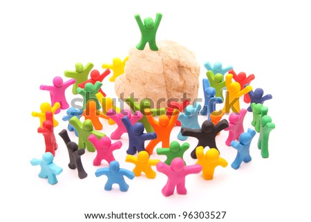 cheerful green plasticine guy standing on top of a rock podium surrounded and acclaimed by lots of colorful people - leadership concept - isolated on white