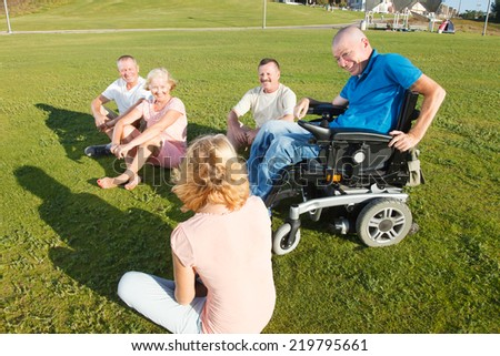 Cheerful group of adult people sitting on the grass. - stock photo