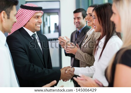 cheerful group of business team welcoming arabian businessman - stock photo