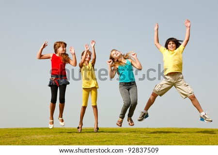 Cheerful group of children resting on the grass - stock photo