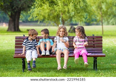 Cheerful Group of Children Sitting on Park Bench - stock photo