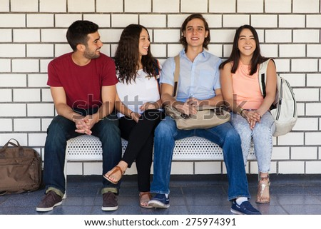 Cheerful group of college friends hanging out in the school hallway - stock photo