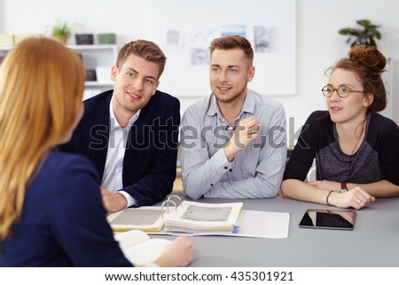 Cheerful group of four colleagues reviewing manuals on gray desk with tablet computer beside it at work - stock photo