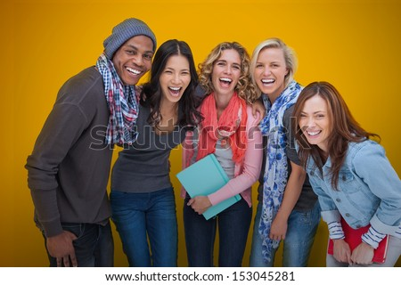 Cheerful group of friends laughing together on yellow background - stock photo