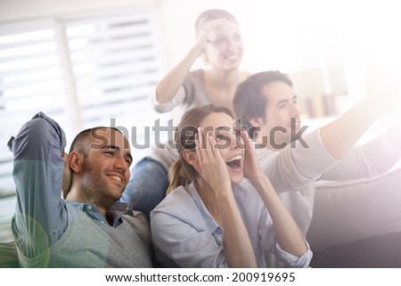 Cheerful group of friends watching football game on tv - stock photo