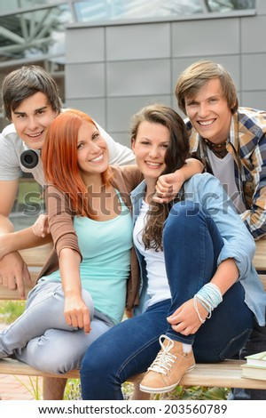 Cheerful group of high school friends hanging out outside campus - stock photo