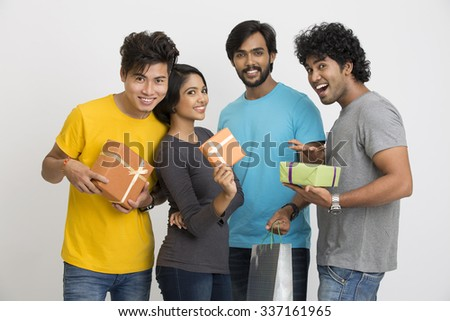 Cheerful group of Indian young friends holding gift boxes on a white background. - stock photo