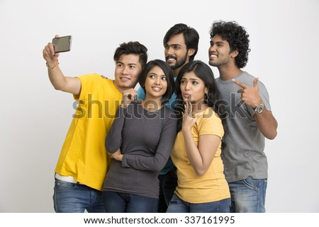 Cheerful group of Indian young friends taking selfie in mobile on a white background. - stock photo