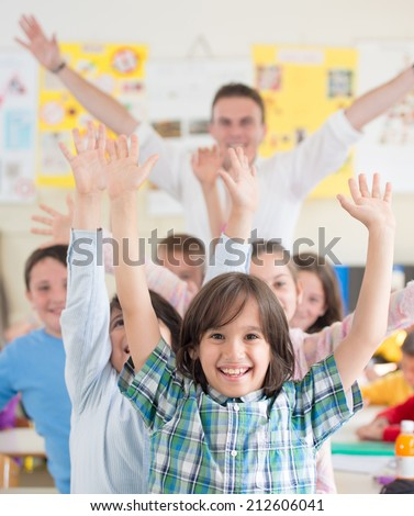 Cheerful group of kids wtih their teacher in school classroom - stock photo