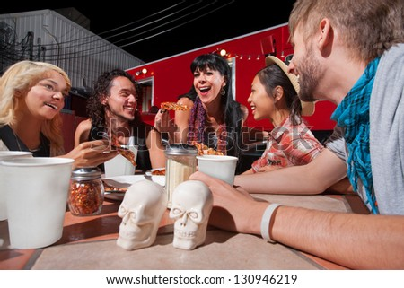 Cheerful group of people with pizza slices outside near food truck - stock photo