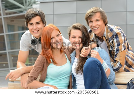 Cheerful group of student friends hugging together outside college - stock photo