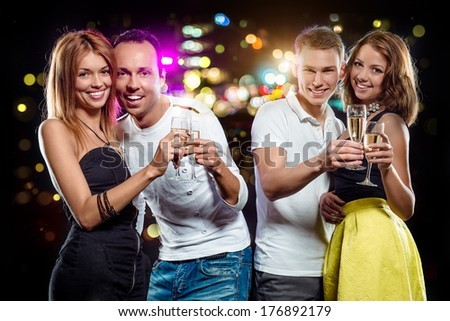 Cheerful group of young people with glasses of sparkling champagne over abstract background - stock photo