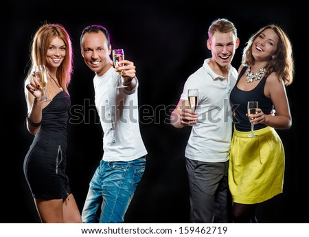 Cheerful group of young people with glasses of sparkling champagne over black background  - stock photo
