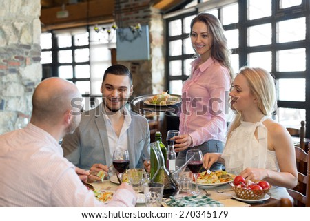 Cheerful group people having dinner at rural restaurant and drinking wine. Focus on the young man - stock photo