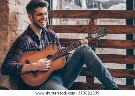 Cheerful guitarist. Cheerful handsome young man playing guitar and smiling while sitting at windowsill  - stock photo