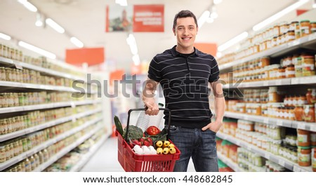 Cheerful guy holding a shopping basket full of groceries and posing in a supermarket - stock photo