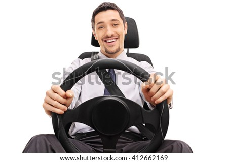 Cheerful guy holding a steering wheel seated on a car seat isolated on white background - stock photo