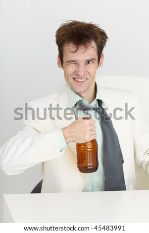 Cheerful guy in a white jacket with a bottle of beer in his hand - stock photo