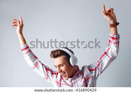 Cheerful guy is enjoying cool song - stock photo