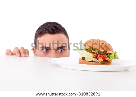 Cheerful guy is hiding behind a table and peeping through it. He is looking at an unhealthy hamburger with desire. Isolated on background - stock photo