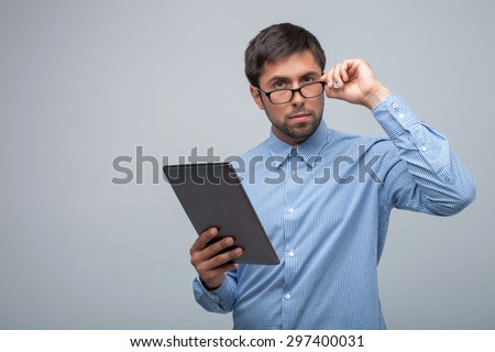 Cheerful guy is holding a tablet in his hand. He is touching his eyeglasses and looking forward seriously. Isolated on grey background and copy space in left side - stock photo