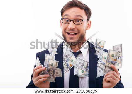 Cheerful guy is holding money and is showered by it. He is smiling with pleasure. Isolated on white background and there is copy space in the left side - stock photo