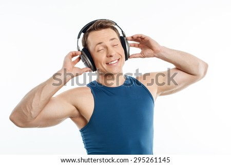 Cheerful guy is listening to music with pleasure. He is touching headphones and smiling. His eyes are closed with enjoyment. Isolated on background - stock photo