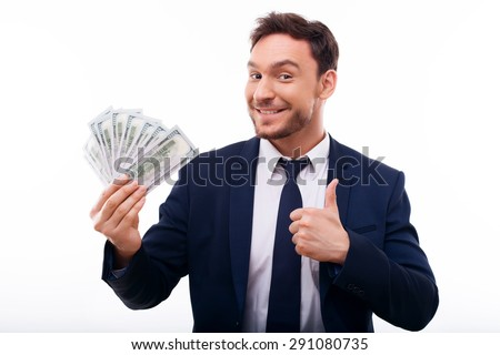 Cheerful guy is smiling and holding money. He is showing thumb up sign. The man is looking at the camera confidently - stock photo