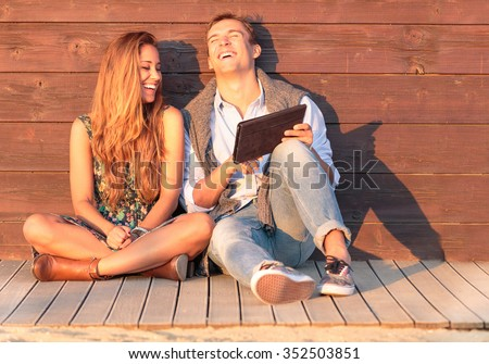 Cheerful guy with girl laugh about video on the tablet. Best friends having fun at the beach with social media and funny contents. Friendship of young people during holiday life moment at sunset. - stock photo
