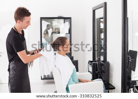 Cheerful hairdresser is holding a white towel. He is drying female hair with it after washing. The woman is sitting and looking at the mirror with joy. They are smiling - stock photo