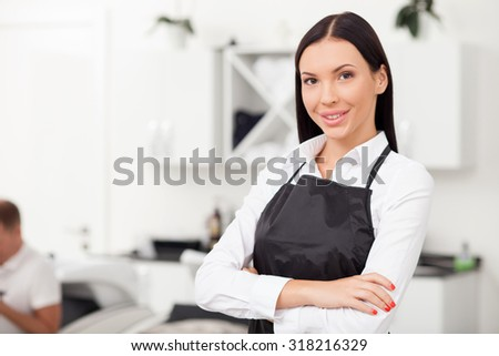 Cheerful hairdresser is standing in beauty shop. She is looking at the camera and smiling. The woman crossed her arms with confidence. Copy space in left side - stock photo