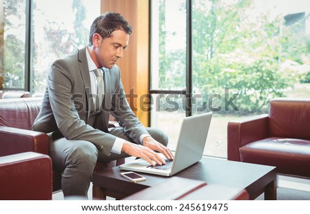 Cheerful handsome businessman working at laptop in the office - stock photo