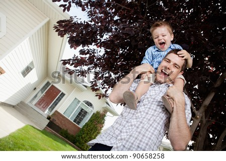 Cheerful handsome father with toddler son on his shoulders - stock photo