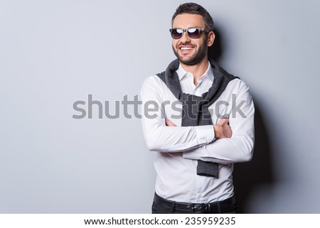 Cheerful handsome. Handsome young man in sunglasses and smart casual wear keeping arms crossed and smiling while standing against grey background - stock photo