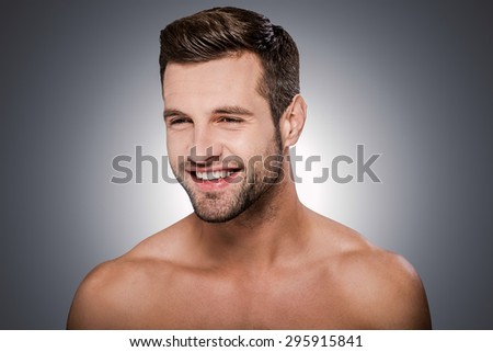 Cheerful handsome. Portrait of handsome young shirtless man looking away and smiling while standing against grey background - stock photo