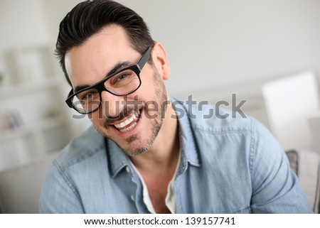 Cheerful handsome trendy guy with glasses - stock photo
