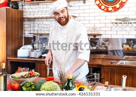 Cheerful handsome young chef cook cutting meat and making vegetable salad on the kitchen - stock photo