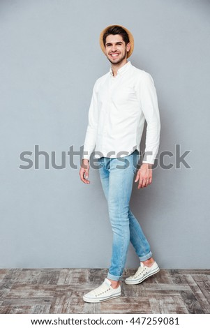 Cheerful handsome young man in white shirt, jeans and hat smiling and walking over grey background