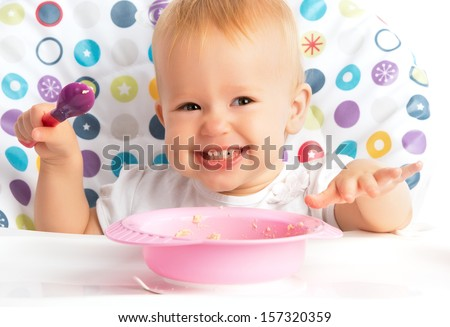 cheerful happy baby child eats itself with a spoon - stock photo