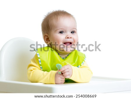cheerful happy baby child sitting in chair with a spoon - stock photo