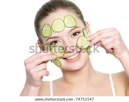 Cheerful happy beautiful girl applying facial mask of cucumber - isolated on white - stock photo