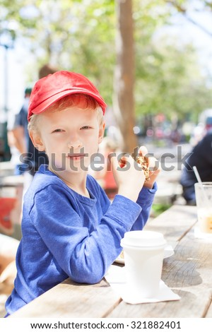 cheerful happy boy sitting in outdoor cafe and enjoying cookie and hot chocolate, urban lifestyle concept - stock photo